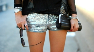 woman-in-silver-shorts-holding-sunglasses-and-a-classic-black-frame-clutch