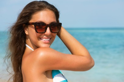 Beautiful Woman Wearing Sunglasses over Sea Background